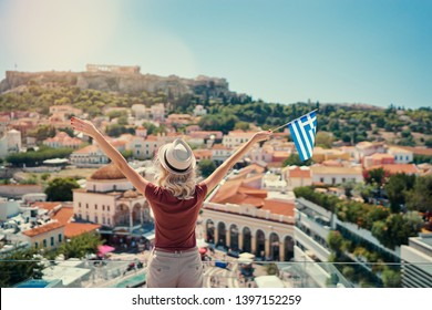 Enjoying vacation in Greece. Young traveling woman with national greek flag enjoying view of Athens city and Acropolis.