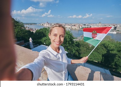 Enjoying vacation in Hungary. Young traveling woman with national hungarian flag taking selfie on view of Budapest city and river.