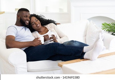 Enjoying Weekend. African American Couple In Love Spending Time Together, Drinking Coffee on Couch at Home, Free Space