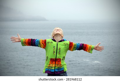 Enjoying the wind. Teenager girl arms raised enjoying the fresh ocean air. Freedom concept.