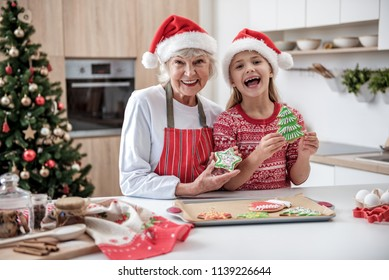 Enjoying winter holidays together. Portrait of happy senior woman standing in kitchen with her granddaughter. They are holding baked colorful cookies and laughing