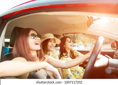 Enjoying woman with her girlfriend   in red car summer vacation, holidays, travel, road trip and people concept .
