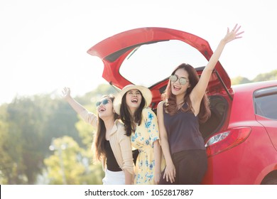 Enjoying woman with her girlfriend traveler sitting on hatchback red car. summer vacation, holidays, travel, road trip and people concept .