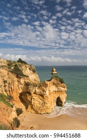 enjoying in wonderful close up view on seascape with stunning huge rocks cliffs with seas caves on sandy camilo beach with waves in colorful sunny blue sky with clouds, algarve, portugal