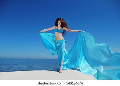 Enjoyment. Beautiful girl enjoying the freshness.  Free happy woman with blowing tissue over blue sky