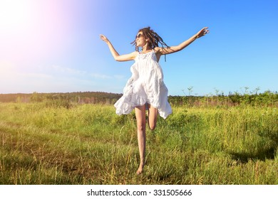 Enjoyment - free happy woman enjoying sunset. Beautiful woman in white dress embracing sunshine glow of sunset with arms outspread and face raised in sky enjoying peace, serenity in nature