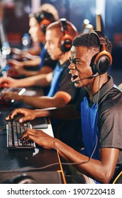 Enjoyment. Side view of a young excited african guy, male cybersport gamer wearing headphones playing online video games while participating with in eSport tournament