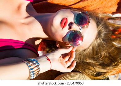 Enjoyment-free happy woman enjoying sunset. Beautiful woman in sensual swimsuit at the golden sunshine glow of sunset sending a kiss to camera and make funny,happy face,reflecting sky in sunglasses.