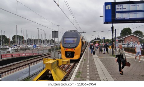 Enkhuizen / Netherlands - August 16 2018: A NS modern Double Decker VIRM train at the railway station of Enkhuizen with boarding passengers