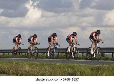 ENKHUIZEN, THE NETHERLANDS - JULY 2 ,2016: Cyclists ride in a row, during a time trial contest for cyclists on the car dike Lelystad and Enkhuizen on july 2 ,2016 in Enkhuizen