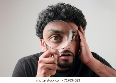 Enlarged eyes of a young man looking through a magnifying glass
