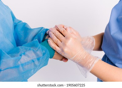 An enlarged photo of the hands where a medical worker in gloves holds the patient's hands as a sign of support. Giving back, volunteer and social assistance