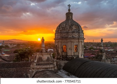 The enlighten dome of the La Merced church in Granada at sunset with Virgin Mary sculptures and the city's skyline, Nicaragua.