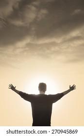 enlightened man with faith praying under god light