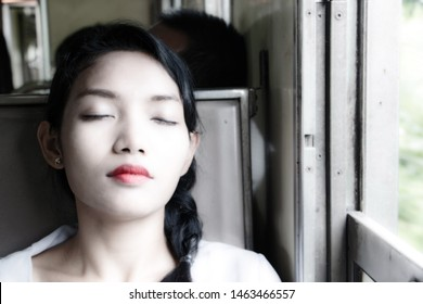 The enlightened portrait of young woman sleeping in the train, soft white light. Passenger sleep in the old wagon of a train