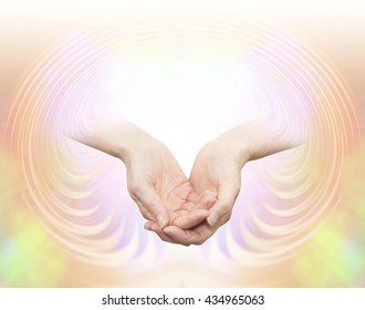 Enlightenment - a pair of female hands in gently cupped position, as if receiving wisdom, emerging from a peach pink draping background with copy space and a white light burst