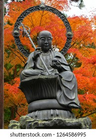 Enmei Jizo bronze statue at Zuigan-ji Temple with autumn maple leaves in autumn Matsushima, Japan. Zuiganji is one of the Tohoku Region most famous and prominent Zen temples.Vertical photo.