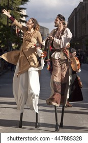 Enna, Italy - May 2016: Stilt walkers man and woman takes part in the medieval costume parade along the street. Tenth Edition of Historical Parade, 15 may 2016, Enna, Sicily