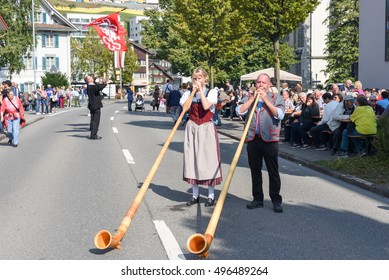 Ennetbuergen, Switzerland - 24 September 2016: People wearing traditional clothes and playing the alphorn at Ennetbuergen on the Swiss alps
