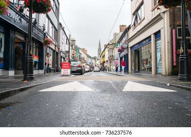 ENNIS, IRELAND - AUGUST 12; Typical small town Ireland street scene on overcast damp day people in street passing shops and signs August 12, 2017 Ennis Ireland