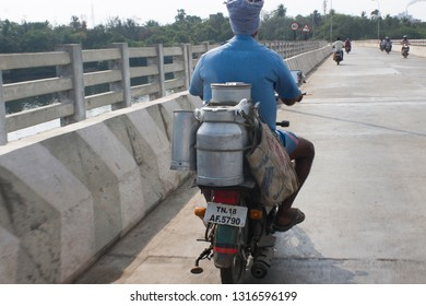 Ennore Creek Bridge, North Chennai, Thiruvallur District, Tamil Nadu in India on February 10, 2019: Milkman carrying milk for customers in Aluminum Containers