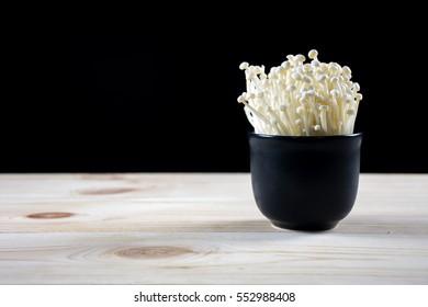 Enoki mushrooms in black bowl on wood table
