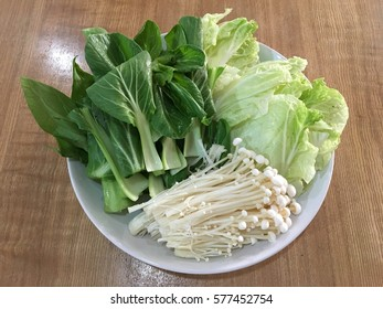 Enoki mushrooms and bok choy and lettuce on a plate placed on a wooden table.