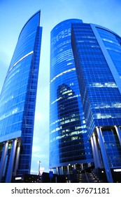 enormous blue skyscrapers from glass and steel at evening