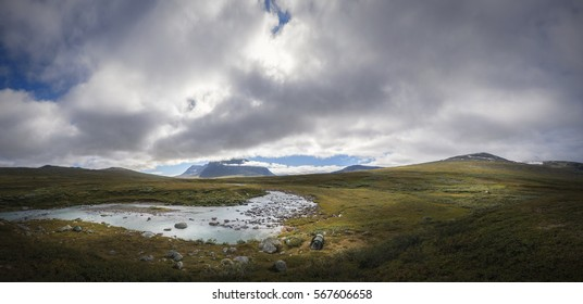 Enormous landscape panorama of Sarek with Sami shelter and tents on river bank trekking in Sweden