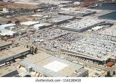 Enormous parking lots with thousands of vehicles near Barselona port and Mediterranean sea in Spain, aerial view. Huge white parking garages and warehouses. Parking scarcity problem in modern cities.
