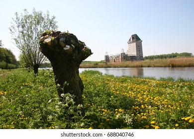 enormous riverside Castle in summer time with cut willow