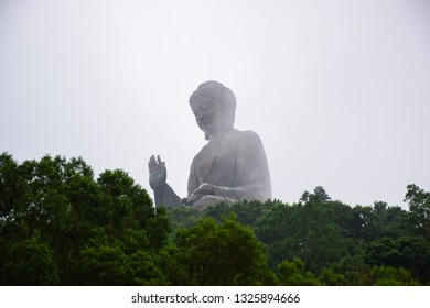 The enormous Tian Tan Buddha statue in the middle of the fog up on high mountain near Po Lin Monastery, Lantau Island, Hong Kong