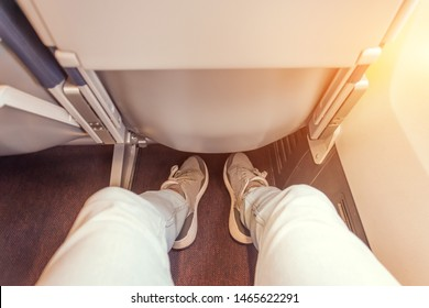 Enough legroom between the seats in the passenger plane, the view of the men's legs. Comfortable flight free space plus