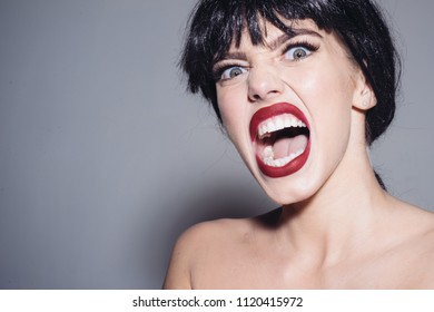 Enraged female in black wig screaming, madness concept. Young woman with furious face isolated on gray background.