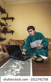 Enraged mature man yelling at his bills and financial reports, dressed in bathrobe, sitting in his living room