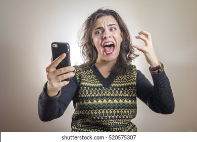 Enraged woman screaming at her cell phone