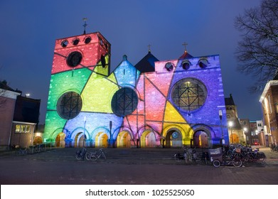 ENSCHEDE, NETHERLANDS - DEC 22, 2017: In the centre of the Dutch city Enschede the Jacobus chuch is being lighted by a beamer with changing colours because of christmas time.