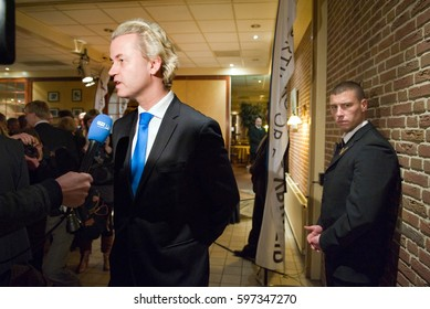 ENSCHEDE, NETHERLANDS - JAN 10, 2011: Political leader Geert Wilders of the Dutch center right party PVV is giving an interview while a body guard is protecting him