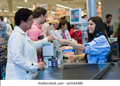 ENSCHEDE, THE NETHERLANDS - JUNE 27: A female cashier of the Albert Heijn supermarket is giving a woman her receipt for the products that she just bought and paid, June 27, 2013 in the Netherlands.