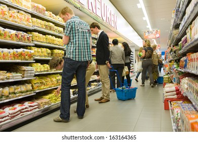 ENSCHEDE, THE NETHERLANDS - JUNE 27: People are looking and shopping in the Albert Heijn supermarket between al the products in a gangway, June 27, 2013 in the Netherlands.