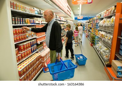 ENSCHEDE, THE NETHERLANDS - JUNE 27: People are looking, walking and shopping in the Albert Heijn supermarket between al the products in a gangway, June 27, 2013 in the Netherlands.
