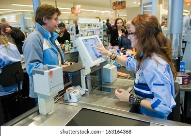 ENSCHEDE, THE NETHERLANDS - JUNE 27: A woman is paying het products that she has bought in the Albert Heijn supermarket at a female cashier, June 27, 2013 in the Netherlands.