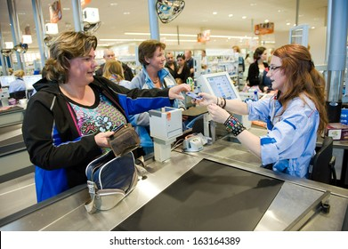 ENSCHEDE, THE NETHERLANDS - JUNE 27: A woman is paying the products that she has choosen in the Albert Heijn supermarket, at a female cashier with a creditcard,  June 27, 2013 in the Netherlands.