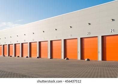 ENSCHEDE, NETHERLANDS - NOVEMBER 28, 2015: Exterior of a commercial warehouse with orange roller doors