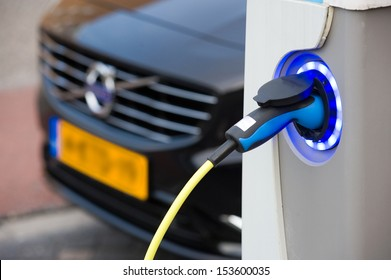 ENSCHEDE, The NETHERLANDS - SEPT 08: An electric car is parked at a parking spot in the center of a town while he is being recharged at a power station, September 08, 2013 in the Netherlands.
