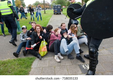 ENSCHEDE, THE NETHERLANDS - SEPT 17, 2017: Left wing protestors are blocking the road during an demonstration of Pegida. Pegida is a group of people who are against the islamization of Europe.