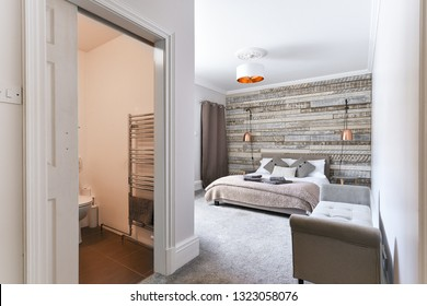 En-Suite Modern Bedroom with rustic wooden headboard and white linen and pillows, copper lamp shade - Airbnb accommodation