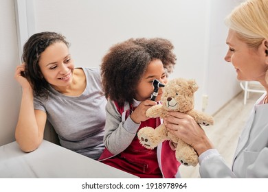 ENT doctor checking African female kid's ear using an otoscope. Hearing exam for children