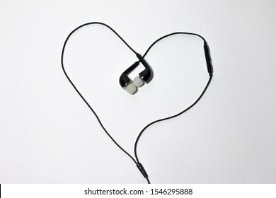 Entangled Black Telephone Earphones isolated on White Background in the Shape of a Heart