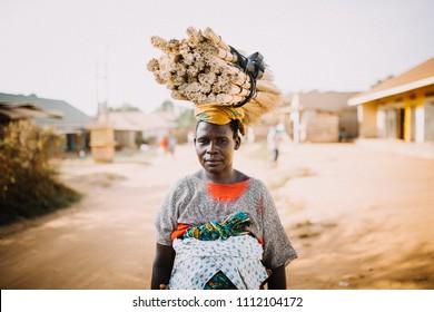 ENTEBBE, UGANDA - FEBRUARY 05, 2018: Woman carrying branches on her head in Entebbe, Uganda.